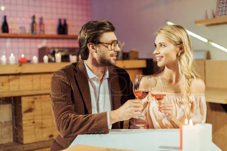 cheerful couple clinking by wine glasses during date at table in cafe