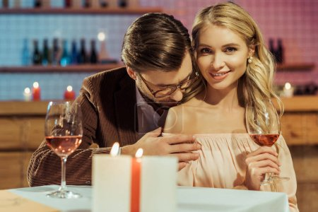 smiling girl with wine glass looking at camera while her boyfriend kissing her shoulder at table in restaurant