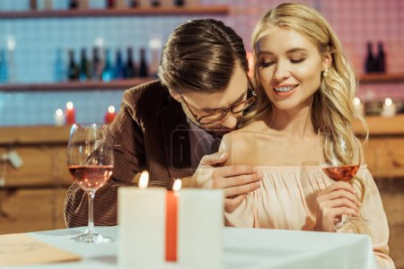 stylish man in jacket kissing beautiful girlfriend during romantic dinner at restaurant