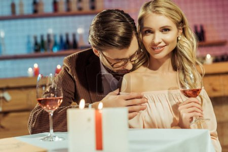 beautiful young woman with wine glass looking at camera while her boyfriend kissing her shoulder at table in cafe