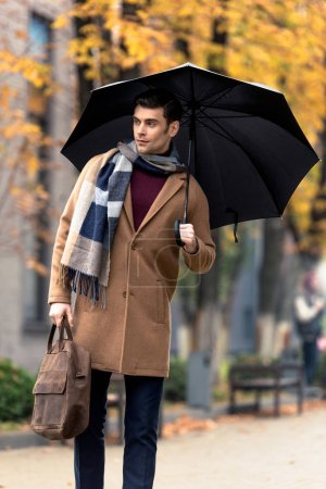 Photo pour Homme élégant séduisant en couche avec parasol à pied par la rue automnale - image libre de droit