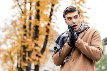 Photo pour Vue de dessous de séduisante homme élégant au manteau de gel automnal rue - image libre de droit