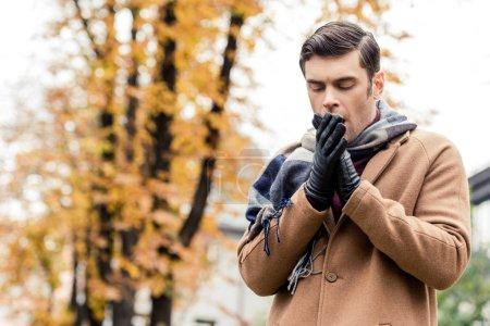 Photo pour Vue du dessous de l'élégant homme au manteau de gel automnal rue - image libre de droit