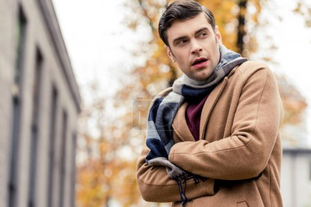 bottom view of handsome man in coat freezing on autumnal street