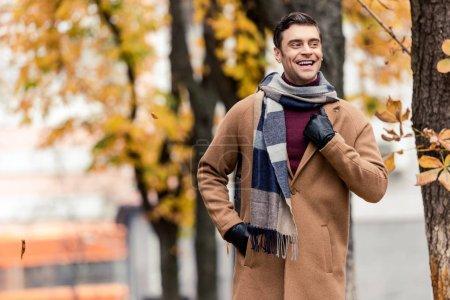 Photo pour Heureux homme élégant au manteau en cours d'exécution par la rue automnale - image libre de droit