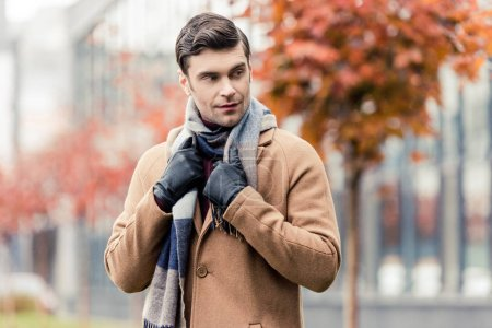 stylish man in coat, leather gloves and scarf standing on autumnal street