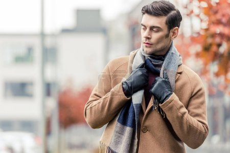 handsome man in coat, leather gloves and scarf standing on autumnal street