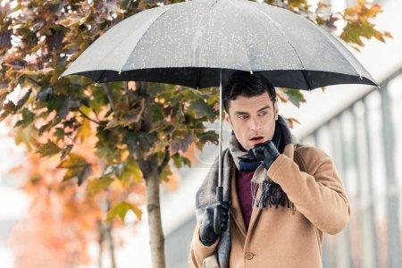 Photo pour Bel homme élégant avec parapluie debout sur la rue automnale - image libre de droit