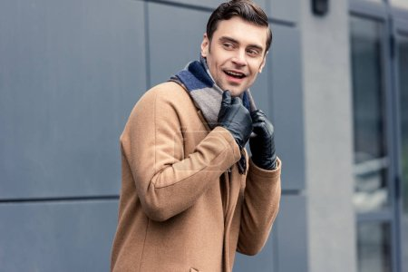 Photo for Handsome smiling man in coat and scarf looking away on street - Royalty Free Image