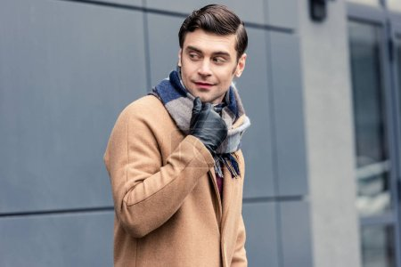 handsome man in coat and scarf looking away on street