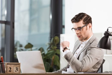 handsome thoughtful businessman working with laptop at modern office