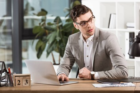 handsome confident businessman sitting at workplace and looking away in modern office