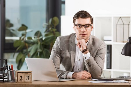 handsome confident businessman sitting at workplace and looking at camera in modern office