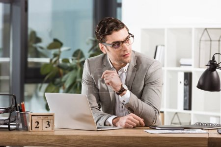 handsome businessman sitting at workplace and looking away in modern office