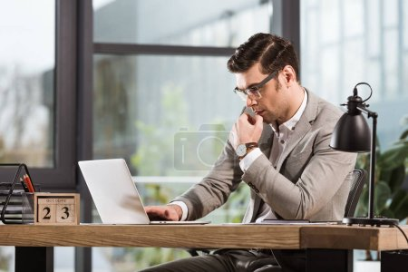 handsome concentrated businessman working with laptop at office