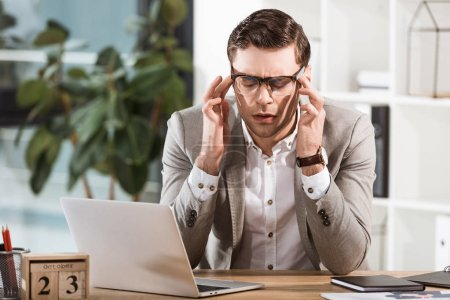 overworked businessman suffering from headache while sitting at workplace in office