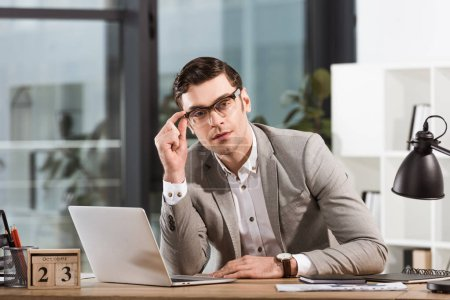 handsome businessman with eyeglasses sitting at workplace in office and looking at camera