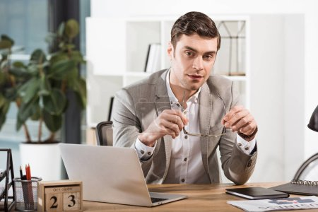 handsome businessman with eyeglasses looking at camera at office