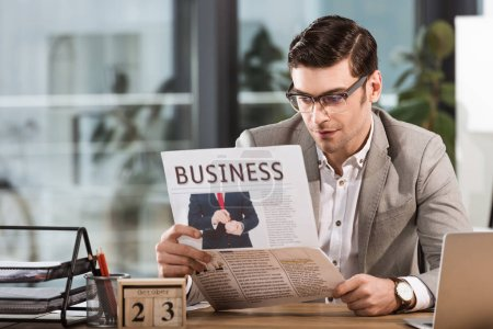 handsome businessman reading newspaper at workplace in office