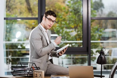 handsome businessman with notebook sitting at workplace at office and looking at camera