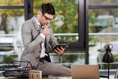focused handsome businessman with notebook sitting at workplace at office