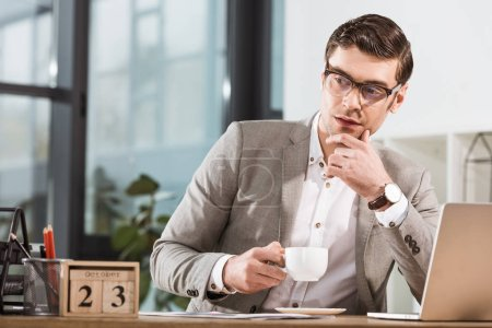 thoughtful handsome businessman with cup of coffee looking away at office