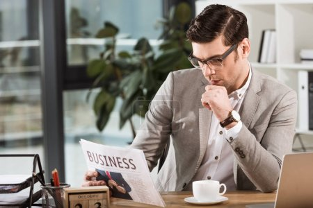 focused handsome businessman with cup of coffee reading newspaper at workplace