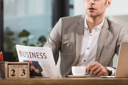 cropped shot of handsome businessman with cup of coffee reading newspaper at workplace