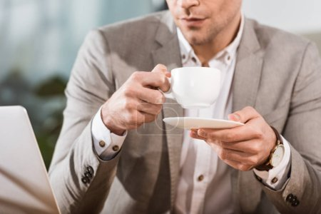 cropped shot of businessman drinking coffee at workplace