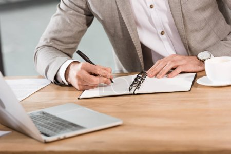 Photo for Cropped shot of businessman writing in notebook at workplace - Royalty Free Image