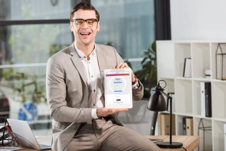 Photo for Handsome happy businessman sitting on desk at workplace and holding tablet with instagram website on screen - Royalty Free Image