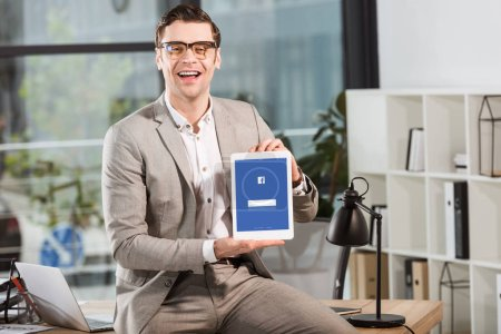 handsome happy businessman sitting on desk at workplace and holding tablet with facebook website on screen