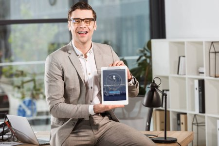 handsome happy businessman sitting on desk at workplace and holding tablet with tumblr website on screen