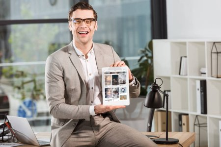 handsome happy businessman sitting on desk at workplace and holding tablet with pinterest website on screen