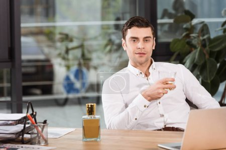 handsome businessman with glass of whiskey sitting at workplace in office and looking at camera