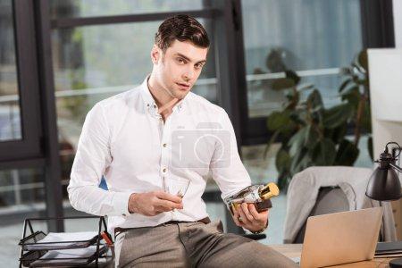 Photo pour Bel homme d'affaires assis sur la table au bureau et en maintenant la bouteille de whisky - image libre de droit