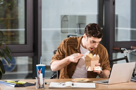 hungry businessman eating take away noodles from box at office