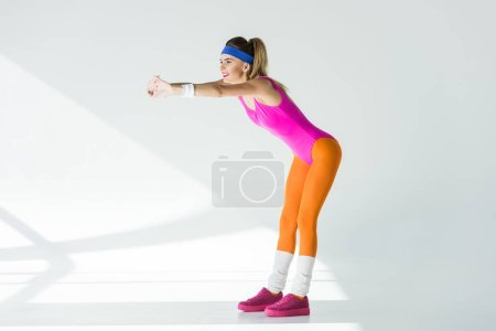 Photo for Side view of smiling athletic woman stretching arms and looking away on grey - Royalty Free Image