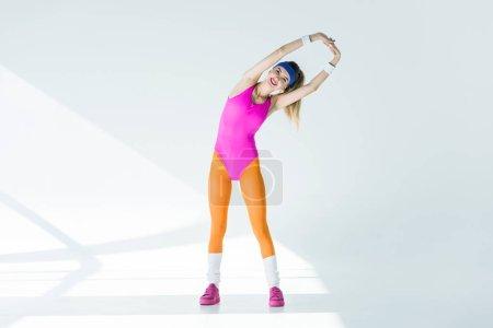 longitud total opinión deportiva joven mujer estirando los brazos y sonriendo a cámara en gris
