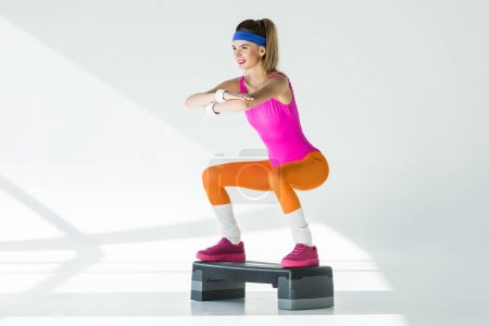 athletic young woman doing squats on step platform and looking away on grey