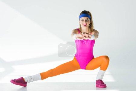 Photo pour Femme heureuse athlétique qui s'étend et souriant à la caméra sur fond gris - image libre de droit
