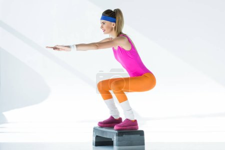 smiling sporty girl training on step platform and looking away on grey