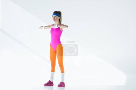 sporty young woman training at aerobics workout on grey