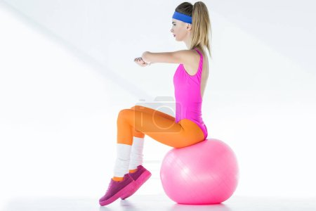 Photo for Side view of athletic young woman sitting and training on fit ball on grey - Royalty Free Image