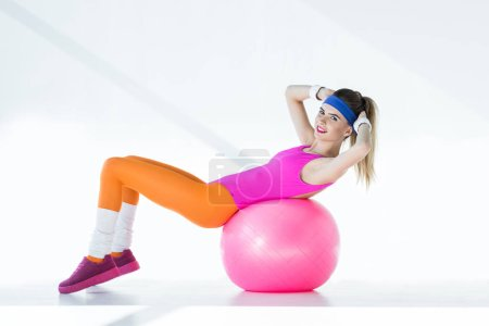 sporty young woman doing abs on fit ball and smiling at camera on grey
