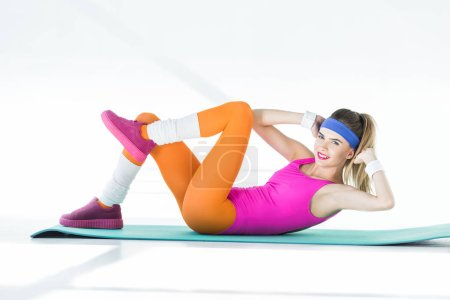 athletic young woman exercising on yoga mat and smiling at camera on grey