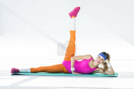 athletic young woman training on yoga mat and smiling at camera on grey
