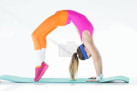 side view of athletic young woman doing bridge exercise on yoga mat on grey