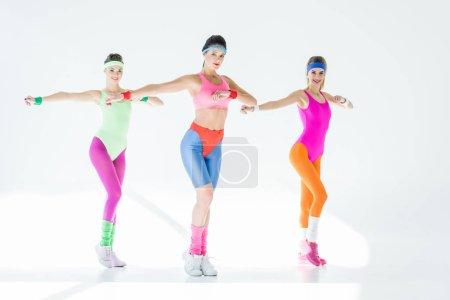 Athlétisme jeunes femmes exerçant ensemble et regardant la caméra sur fond gris
