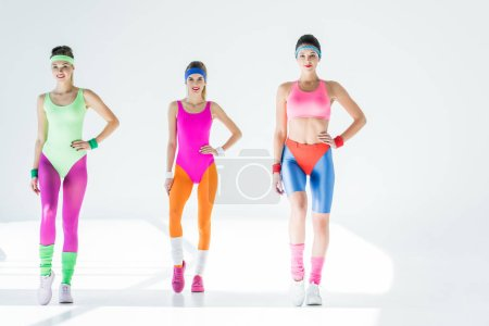 smiling sporty girls exercising at aerobics workout on grey